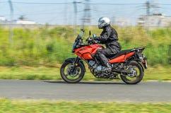 摩托车的摩托车骑士在乡下公路去 背景迷离弄脏了抓住飞碟跳的行动 免版税库存图片