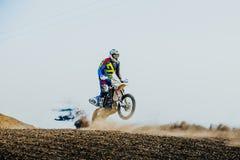 摩托车的竟赛者在一条多灰尘的轨道的后轮乘坐 免版税库存图片