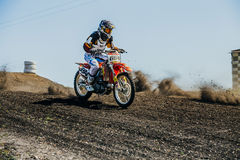 摩托车的竟赛者在多灰尘的轨道乘坐 库存照片
