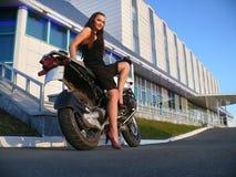 摩托车的美丽的女孩。 库存图片