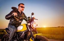 摩托车的骑自行车的人 库存照片