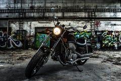 摩托车砍刀在有都市的街道画的一个老工业大厅里 免版税图库摄影