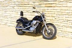 摩托车站立近的砖墙的本田马VLX 库存图片