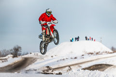 摩托车竟赛者跳高和飞行  免版税库存照片