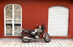 摩托车红色墙壁 库存照片