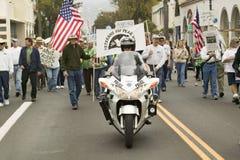 摩托车警察导致抗议者游行乔治W.布什和伊拉克战争在反伊拉克战争抗议游行在圣芭卜拉,在2007年3月17日的加利福尼亚 布什和伊拉克战争在反伊拉克战争抗议游行在圣 免版税库存照片