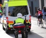 摩托车警察,当护航在交通时的一辆救护车 库存图片