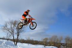 摩托车越野赛冬天,在随风飘飞的雪的高飞行摩托车竟赛者 库存照片