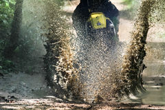 摩托车越野赛横穿小河,水飞溅 库存图片