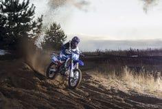 摩托车越野赛车手创造尘土和残骸云彩  免版税图库摄影