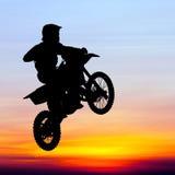 摩托车越野赛车手剪影在天空跳跃 库存照片