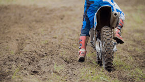 摩托车越野赛骑他的土十字架MX自行车-背面图的竟赛者开始 库存图片
