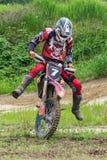 摩托车越野赛 运动员在摩托车的前轮移动 免版税库存照片