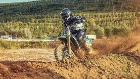 摩托车越野赛MX在泥铺跑道的车手骑马 免版税库存图片