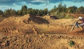摩托车越野赛MX在泥铺跑道的车手骑马 图库摄影