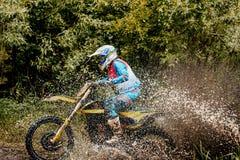 摩托车车手十字架水坑飞溅水和dir 免版税库存照片