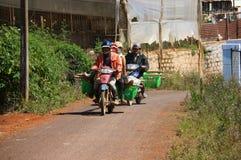 摩托车运载农夫在工作日以后回家 图库摄影