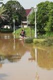 摩托车通过洪水 库存图片