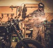 摩托车风俗车库的技工 免版税图库摄影