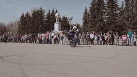 摩托车骑士在它的后腿上在位子把自行车放并且乘坐它站立 股票视频