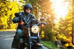 摩托车骑士在路的骑马砍刀 库存图片