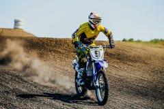 摩托车骑士沿多灰尘的路乘坐的运动员 图库摄影