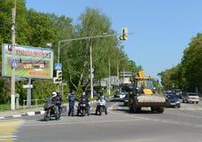 摩托车骑士的警察检查文件的官员交叉点的 库存照片
