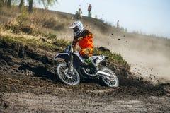 摩托车滑行的竟赛者打开一条多灰尘的赛马跑道 库存图片