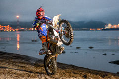 摩托车Enduro在海滩的骑马自行车前轮离地平衡特技 免版税库存照片