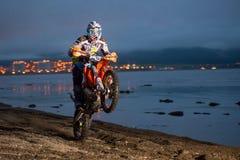 摩托车Enduro在海滩的骑马自行车前轮离地平衡特技 库存照片