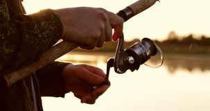 摩擦卷轴钓鱼竿特写镜头在美好的日落的背景的 股票视频