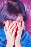 摩擦她的眼睛的一名疲乏的妇女 免版税库存图片