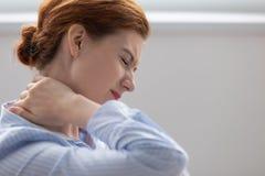 摩擦斜颈的疲乏的被疲劳的女商人感觉创伤 免版税库存照片