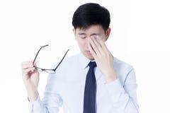 摩擦他疲乏的眼睛的年轻亚洲商人从长时间工作使用计算机 免版税库存图片