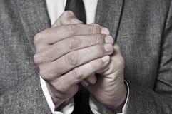摩擦他的手的衣服的人 免版税库存图片