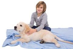 摩擦他的狗的孩子说谎在毯子 免版税库存图片