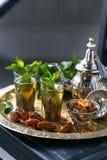 摩洛哥茶用在传统玻璃的薄菏,在一块铜版的铜茶壶 免版税库存图片