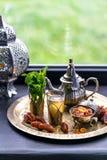 摩洛哥茶用薄菏和糖在一块玻璃在一块铜版有水壶的 库存照片