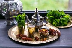 摩洛哥茶用薄菏和糖在一块玻璃在一块铜版有水壶的 免版税库存照片