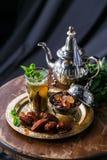 摩洛哥茶用薄菏和糖在一块玻璃在黑暗的背景 免版税图库摄影