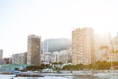 摩纳哥,欧洲- 2017年在日落期间的8月16日城市 国际商业中心摩纳哥 太阳通过旅馆和busin是光亮的 库存图片