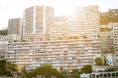 摩纳哥,欧洲- 2017年在日落期间的8月16日城市 国际商业中心摩纳哥 太阳通过旅馆和busin是光亮的 免版税库存图片