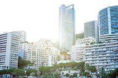 摩纳哥,欧洲- 2017年在日落期间的8月16日城市 国际商业中心摩纳哥 太阳通过旅馆和busin是光亮的 免版税库存照片