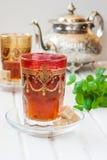摩洛哥茶用薄菏和糖在一块玻璃在一张白色桌上与水壶 免版税图库摄影