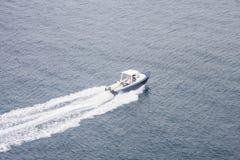 撇取在水间的空白和蓝色小船 免版税库存图片