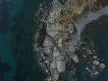 撒丁岛海岸的航拍在夏天日落期间的 在岩石的小波浪采取与寄生虫 库存图片