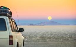 撒拉族在月亮日落的De Uyuni -在玻利维亚冒险汽车旅行 库存照片