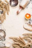 撒粉于烘烤背景用未加工的鸡蛋、滚针和麦子耳朵 免版税图库摄影