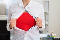 撕毁她的衬衣的女实业家显示红色服装 免版税库存照片