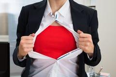 撕毁她的衬衣的女实业家显示红色服装 免版税图库摄影